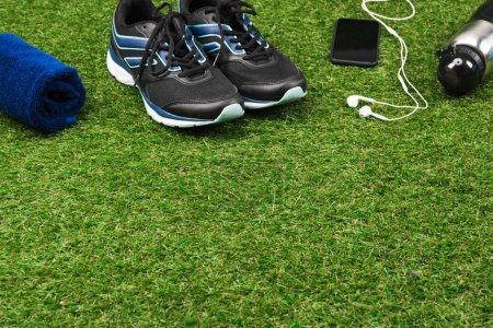 trainers with smartphone and sport bottle on grass