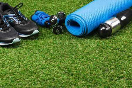 1 trainers with jump rope and dumbbells on grass