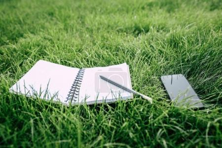 Photo for Close-up view of smartphone with blank screen, empty notebook and pencil on green grass - Royalty Free Image