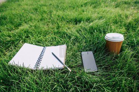 Photo for Close-up view of notebook with pencil, smartphone with blank screen and disposable coffee cup on green lawn - Royalty Free Image