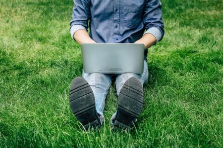 Foto de Sección baja de joven usando laptop mientras descansas sobre la hierba verde - Imagen libre de derechos