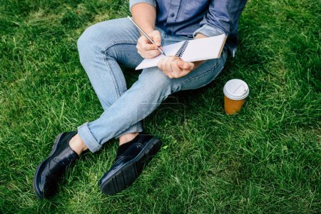 Photo for Cropped shot of man writing on notebook and drinking coffee from paper cup while sitting on green grass - Royalty Free Image