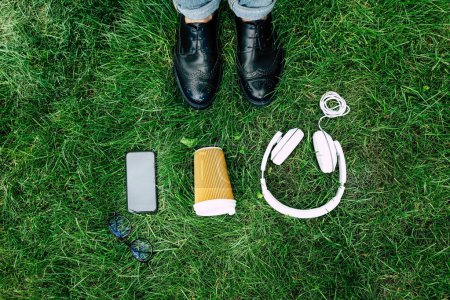 Digital devices and paper cup on grass