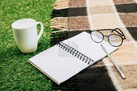 Photo for Close up view of blank notebook with pencil and eyeglasses on blanket - Royalty Free Image