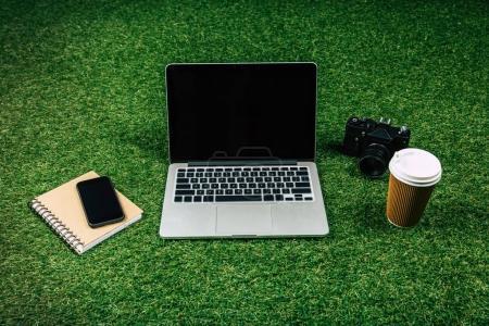 Photo pour Ordinateur portable, smartphone, appareil photo et le café pour aller dans le gobelet jetable sur l'herbe verte - image libre de droit