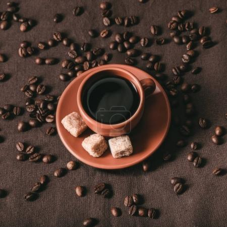 Photo for Top view of ceramic coffee cup with brown sugar cubes and coffee grains on brown cloth - Royalty Free Image