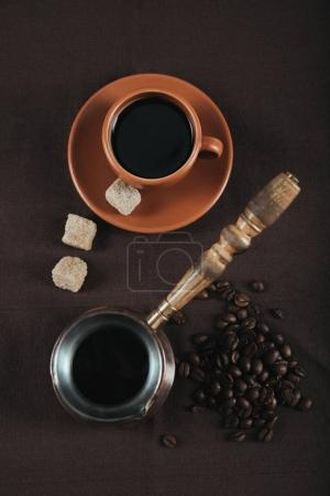 Photo for Traditional coffee turk and ceramic cup with brown sugar cubes and coffee grains on brown cloth - Royalty Free Image