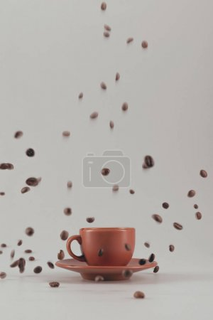 Photo for Ceramic coffee cup with falling coffee grains isolated on grey - Royalty Free Image