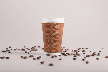 Photo pour Tasse à café jetable avec des grains de café épars isolé sur beige - image libre de droit