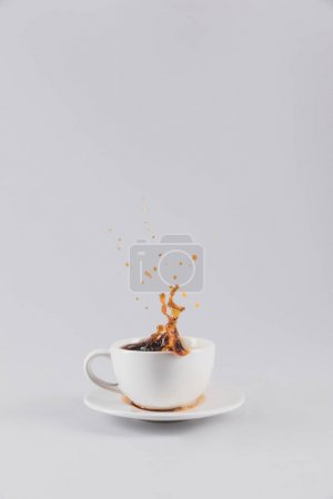 Photo for Coffee splashing out of white cup on saucer, isolated on grey with copy space - Royalty Free Image