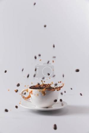 Photo for White coffee cup with falling coffee grains isolated on grey with copy space - Royalty Free Image