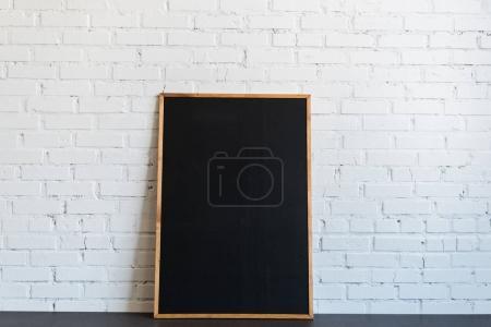 Photo pour Tableau noir vide dans un cadre en bois debout au mur de briques blanches - image libre de droit