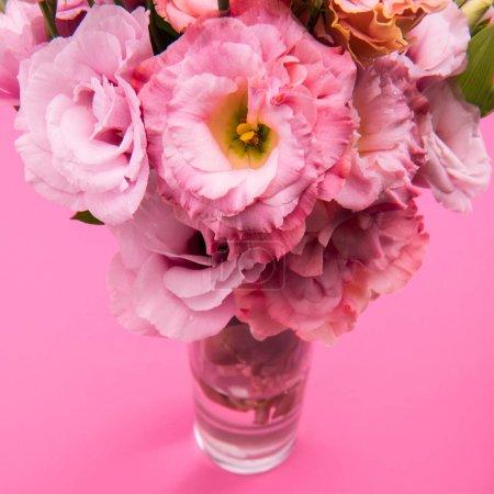 Photo pour Vue rapprochée d'un beau bouquet de fleurs d'eustomes rose tendre dans un vase isolé sur rose - image libre de droit