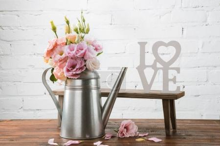 Photo for Beautiful blooming flowers in watering can and small bench with love symbol arranged on wooden surface - Royalty Free Image