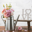 Beautiful blooming flowers in watering can and sma...