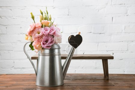 Photo for Beautiful tender flowers in watering can and small bench with heart symbol arranged on wooden surface - Royalty Free Image