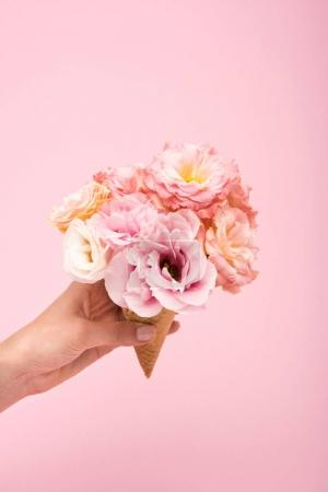 Photo for Cropped shot of person holding waffle cone with beautiful blooming flowers isolated on pink - Royalty Free Image
