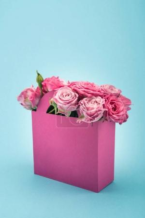Photo for Close-up view of beautiful blooming pink roses in decorative paper bag arranged isolated on blue - Royalty Free Image