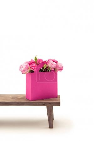 Roses in paper box on bench
