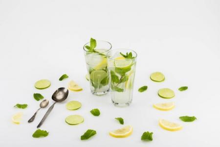 Foto de Bebidas refrescantes cítricos en vasos y cucharas aislados en blanco - Imagen libre de derechos
