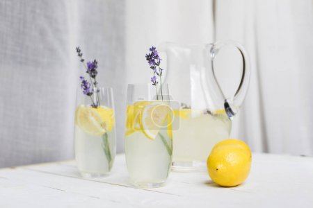 Photo for Close up view of citrus beverages with lavender in glasses and glass jar on wooden table - Royalty Free Image