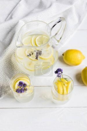 Foto de Vista de ángulo alto caseras bebidas cítricos con flores de lavanda en los vidrios de sobre mesa de madera - Imagen libre de derechos