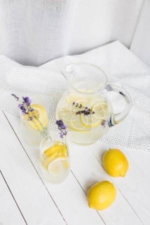 Photo pour Limonade estivale avec des morceaux de lavande et de citron dans des verres et un bocal en verre sur une table en bois - image libre de droit