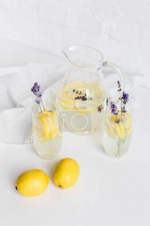 Photo pour Boissons rafraîchissantes de summertime avec des fleurs de lavande dans les verres et jar sur table - image libre de droit