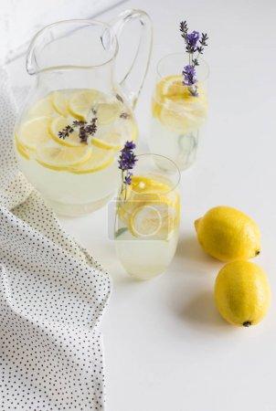 Foto de Bebidas refrescantes del verano con flores de lavanda en vasos y jarra de mesa - Imagen libre de derechos