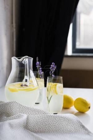 Foto de Refrescante limonada casera con flores de lavanda en vasos y jarra en la mesa en la habitación - Imagen libre de derechos