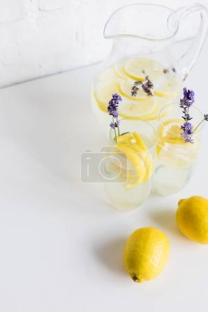 Photo for Summertime homemade lemonade with lavender and lemon pieces in glasses and jar on table - Royalty Free Image