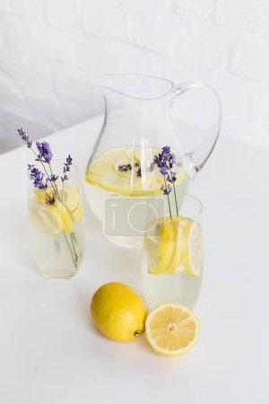 Foto de Refrescante limonada de verano con flores de lavanda en vasos y jarra de mesa - Imagen libre de derechos