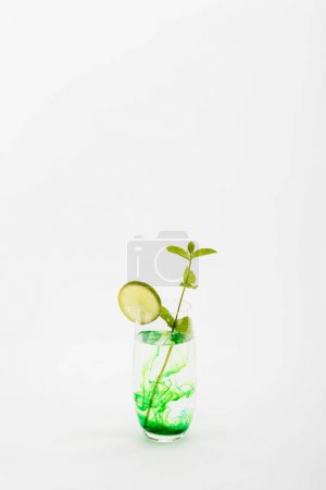 Photo for Refreshing drink with lime and mint twig in glass isolated on white - Royalty Free Image