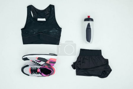 Photo for Top view of sportswear with sneakers and sports bottle isolated on grey - Royalty Free Image