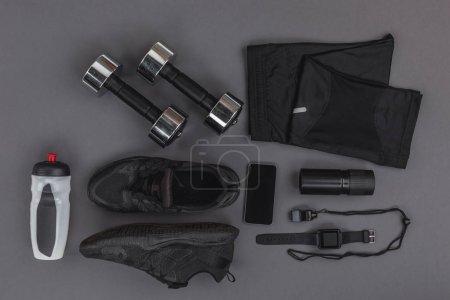 Foto de Lay Flat con ropa deportiva, gimnasio y aparatos aislados en gris - Imagen libre de derechos
