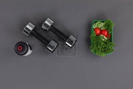 Dumbbells with sports bottle and salad