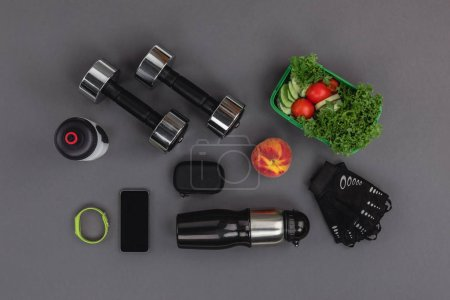 Photo for Top view of smartphone with fitness tracker, dumbbells and vegetable salad isolated on grey - Royalty Free Image