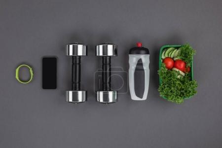Photo for Top view of sports bottle, vegetable salad and digital devices with dumbbells - Royalty Free Image