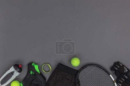 Photo for Top view of tennis equipment and sportswear, fitness tracker and sports bottle isolated on grey - Royalty Free Image