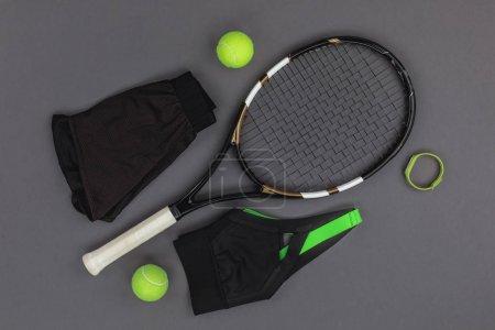 Photo pour Vue de dessus de tennis raquette et balles, sportswear et fitness tracker isolé sur fond gris - image libre de droit