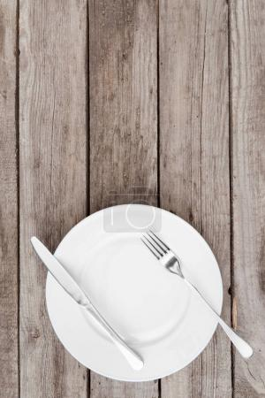 Photo for Top view of arranged empty plate, fork and knife on wooden table - Royalty Free Image