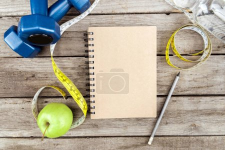 Photo for Top view of notebook, fresh apple, measuring tape and sport equipment on wooden table - Royalty Free Image