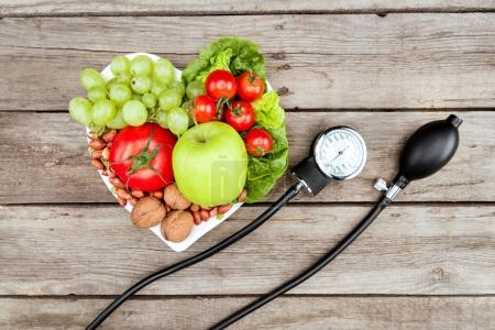 Photo for Top view of fresh various vegetables, fruits and blood pressure gauge on wooden surface, healthy eating concept - Royalty Free Image