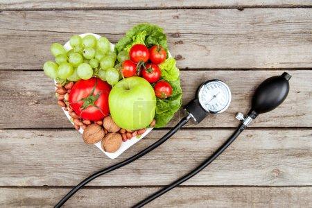 Photo pour Vue de dessus de légumes frais divers, fruits et jauge de pression artérielle sur la surface en bois, concept de saine alimentation - image libre de droit