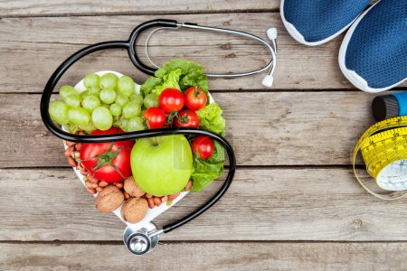 Photo for Top view of stethoscope, organic vegetables and fruits and measuring tape on wooden surface, healthy lifestyle concept - Royalty Free Image