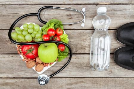 Photo for Top view of stethoscope, organic vegetables and fruits and sport equipment on wooden surface, healthy lifestyle concept - Royalty Free Image