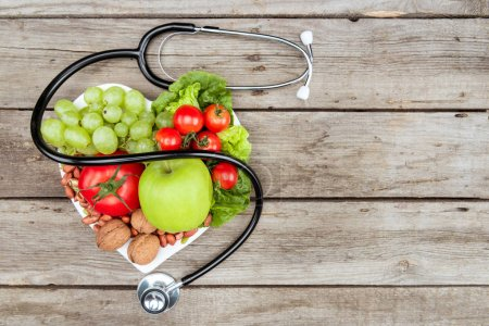 Photo for Top view of stethoscope,various organic vegetables and fruits on wooden surface, clean eating concept - Royalty Free Image