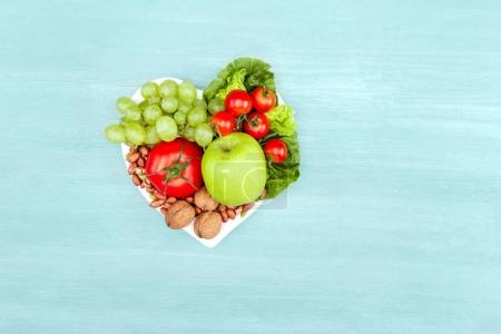 Photo for Top view of fresh organic vegetables and fruits on heart shaped plate isolated on blue, healthy eating concept - Royalty Free Image