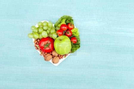 Foto de Vista superior de frutas y vegetales orgánicos frescos en la placa en forma de corazón aislada en concepto de comer sano, azul - Imagen libre de derechos