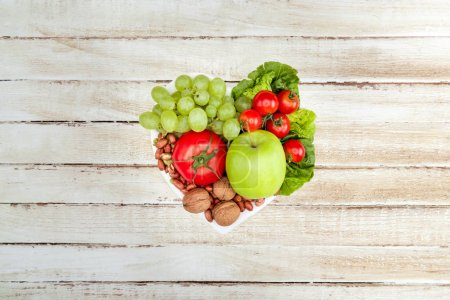 Photo for Top view of fresh organic vegetables and fruits on heart shaped plate, healthy eating concept - Royalty Free Image